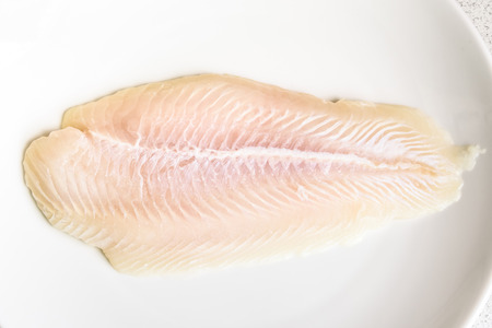 close up, Fillet of raw fresh fish on white plate, selective focus