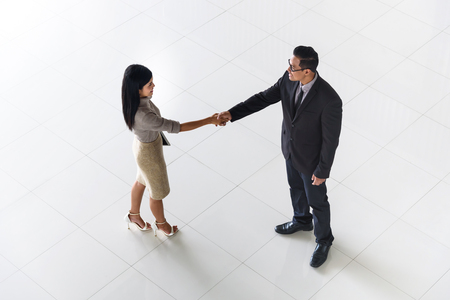 Top view, Asian business people, man and woman, greeting by smiling and shaking hands