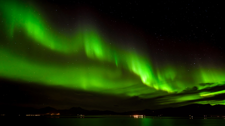 atmosphere: A beautiful green Aurora borealis or northern lights in the sky at Tromso, Norway