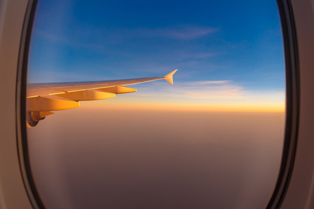 wing of airplane with morning sunrise and blue sky through window Stock Photo