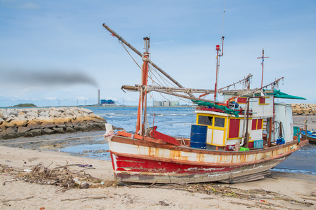 Fishing boat at dirty beach in bad air polution,Concept of Environment effect from petrochemical polution.