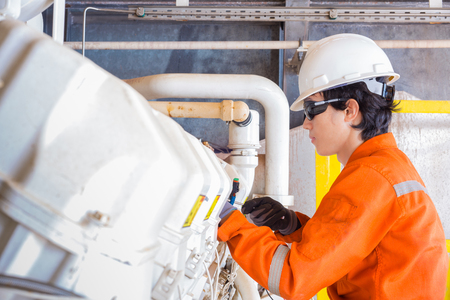Offshore oil and gas multi skill operator ( Electrical, Instrument and Mechanical ) while maintenance gas engine of gas booster compressor at oil and gas wellhead remote platform. Stock Photo