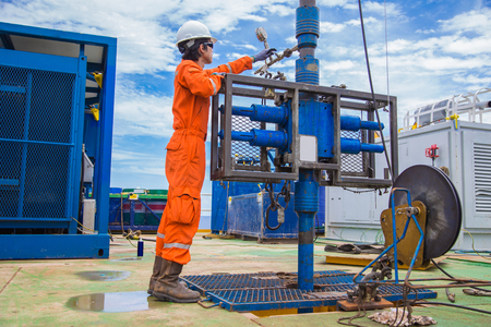 Offshore oil and gas industry, oil rig worker inspect and setting up top side tools for safety first to perforation oil and gas production well.
