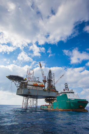 oil and gas industry: Ofshore oil and gas drilling at the gulf of Thailand, Construction crane lifting and loading cargo to supply boat.