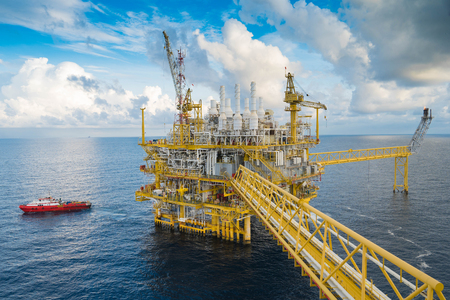 oil and gas industry: Oil and gas central processing platform in the gulf of Thailand. Construction crane transfer cargo to boat.
