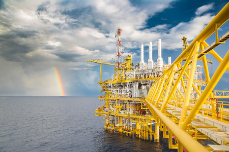 oil and gas industry: Dark cloud, blue sky and rain with rainbow near oil and gas central processing platform in the morning.