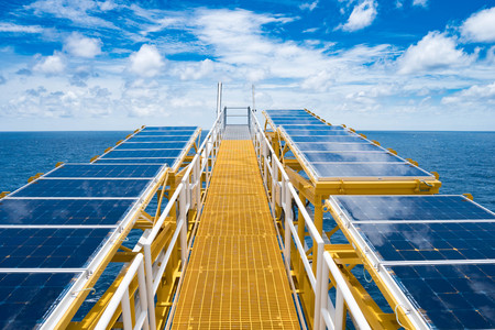 Solar cells at flare bridge at oil and gas wellhead remote platform for charging battery of electrical system on platform. Stock Photo