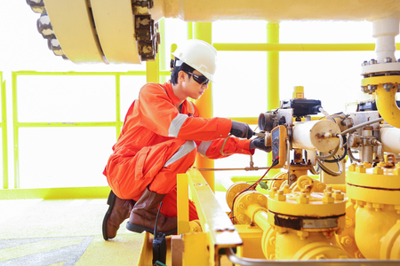 Electrical and Instrument technician is replacing solenoid valve of shut down valve at oil and gas wellhead remote platform, offshore occupational oil and gas business. Standard-Bild