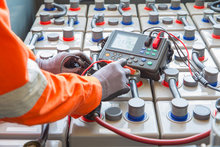 Electrician specialist inspect, check voltage and internal resistance of batteries by using battery to preventive maintenance, offshore oil and gas occupational. Imagens
