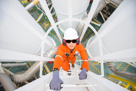 Oil and gas industry worker climb up to pressurized gas vessel for checking  oil and gas dehydration process at the top of vessel. Stockfoto