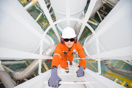 Trabajador de la industria del petróleo y el gas sube al recipiente de gas presurizado para verificar el proceso de deshidratación del petróleo y el gas en la parte superior del recipiente.