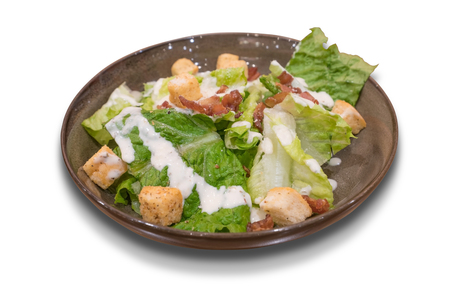 Bowl of traditional Caesar salad with bacon isolated on white background.