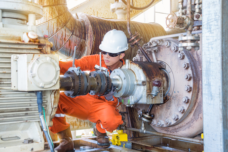 Offshore Oil Rig worker, Mechanical technician inspecting oil centrifugal pump alignment to prevent vibration which damage bearing and mechanical seal systems.
