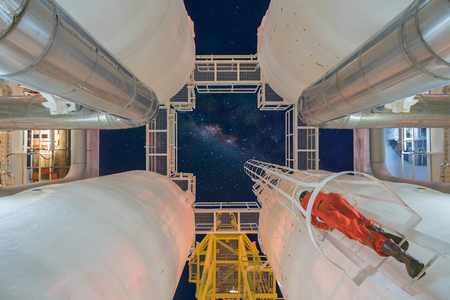 Engineering climb up to oil and gas process plant to observer gas dehydration processing in night shift, offshore maintenance and service, long exposure galaxy milky way.