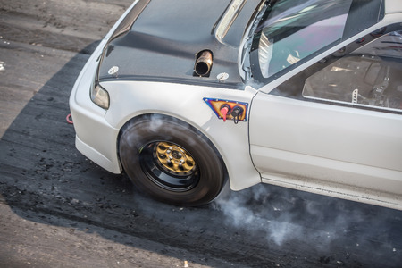 Front wheel drive sport car burning tire for warm up before competition start to increase type temperature for good traction.