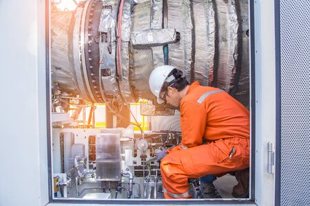 Turbine technician check and inspection gas turbine engine of electric power generator to cross check before startup, offshore oil and gas service occupational. Stockfoto