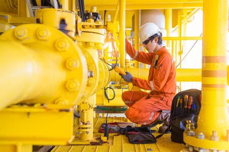 Electrical and instrument technician replace solenoid of shut down valve at offshore oil and gas remote platform, maintenance and service occupational at oil rig.