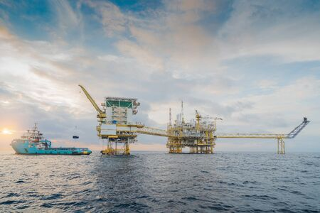 Offshore oil and gas central processing platform where produce raw gas condensate and crude oil for sent to onshore refinery and petrochemical industry, crane lifting cargo to supply boat. Stockfoto