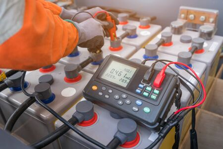 Electrical technician use milliohm meter to measure internal resistance and voltage of batteries which use at offshore oil and gas wellhead remote platform to monitor battery performance.