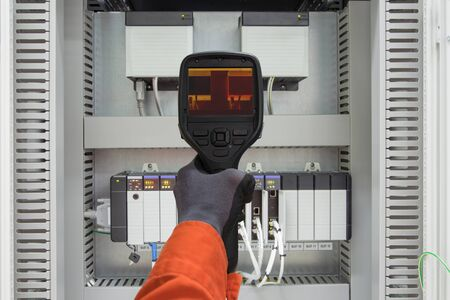 Electrician use thermo scan gun survey loosen cable, wiring and over load electric and instrument equipment to find an abnormal condition, electrical system site service job.