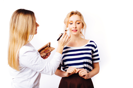 The process of creating makeup. Makeup artist applies bright make-up with a brush on the face of a beautiful young blonde girl in a striped T-shirt.
