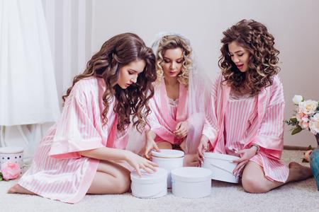 Despedida de soltera. Tres niñas celebran una despedida de soltero o un cumpleaños, dándose regalos en batas de seda rosa. Foto de archivo