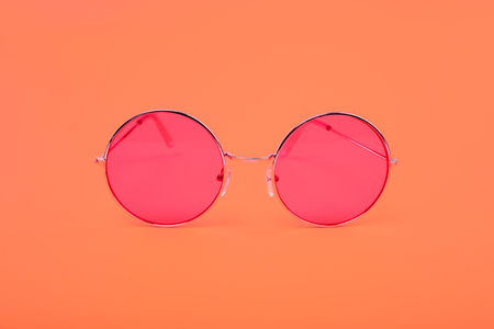 Bright red glasses on the background of the color Living Coral.