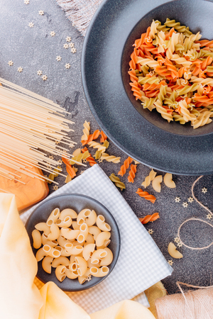 Different types of pasta on a black plate top view.