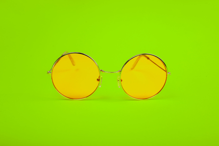 Bright yellow glasses on a green background.