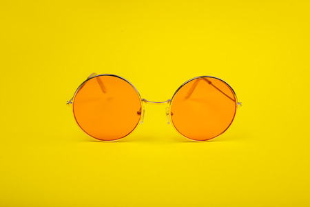 Bright orange glasses on a yellow background.