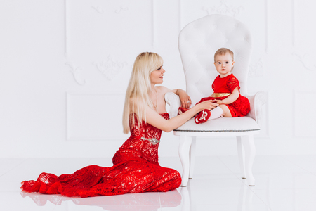 Nice, family, good photo of mother and daughter in red dresses in the studio. Mothers Day and daughters. Advertising family values and traditions.