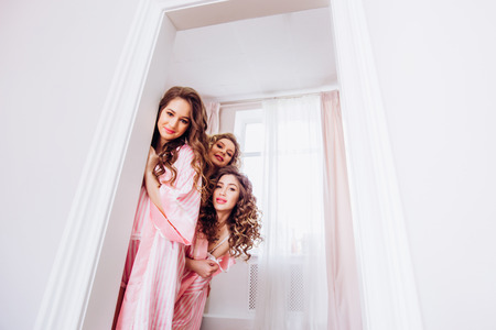 Hen-party. Three girls in pink pajamas peeking out from behind a white door and invited to a party.