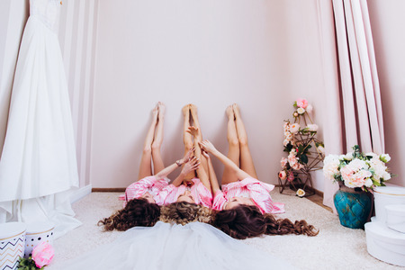 Charming girls lying upstairs with arms raised crossed legs, celebration of a birthday holiday event. Stock Photo