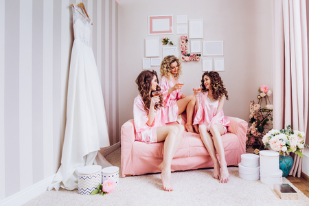 Party for girls. Girlfriends drink pink champagne before the wedding ceremony in pink pajamas.