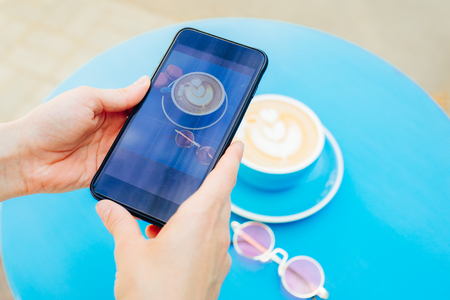 Picture of a coffee on a smartphone on a blue table.