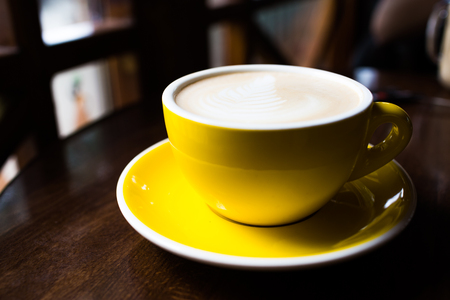 Yellow cup of aromatic coffee on a wooden table.