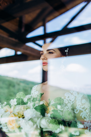 Portrait of a young girl of the bride with professional wedding makeup and hairdo in window. Stock Photo