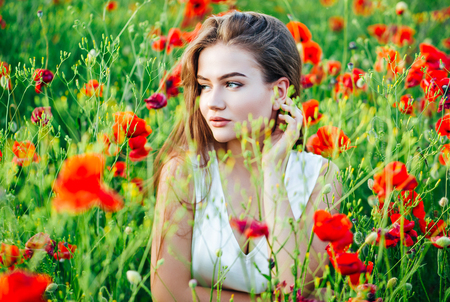Beautiful young girl in poppy fields at sunset. Stock Photo