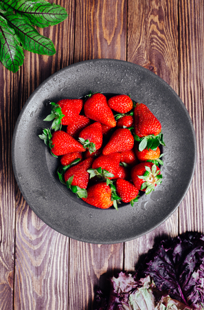 Strawberries in a black plate on a wooden eco background with greens.