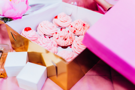 Pink wedding cupcakes for a party in a gold box.