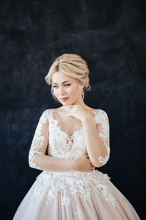 Studio portrait of a young girl of the bride with professional wedding makeup and hairdo. Stock Photo