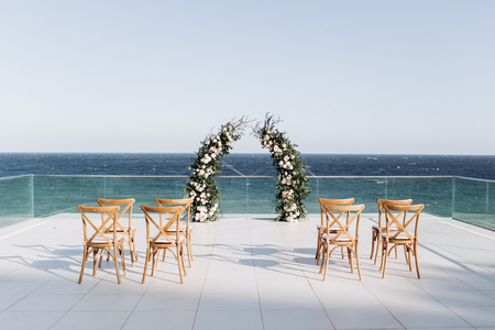Arch decorated with lively floristics on the background of the sea.