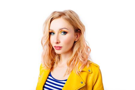 Young blonde girl with an original hairstyle and bright professional makeup