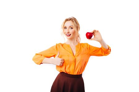 Girl blonde in a bright orange sweater with an apple in her hands promotes healthy food. Imagens