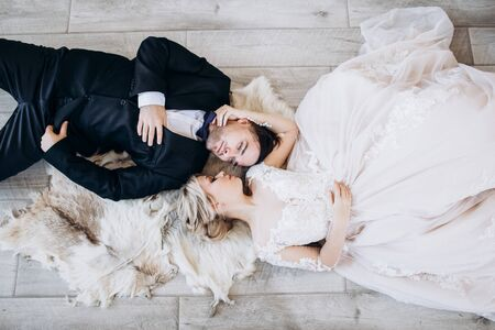 Bride and groom in wedding clothes are lying on the floor and smiling. Stock Photo