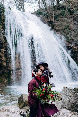 A loving, stylish, young couple in love on the background of a waterfall. 스톡 콘텐츠 - 124982999