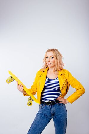 A slender blonde girl with a yellow skate in her hands on an isolated white background.