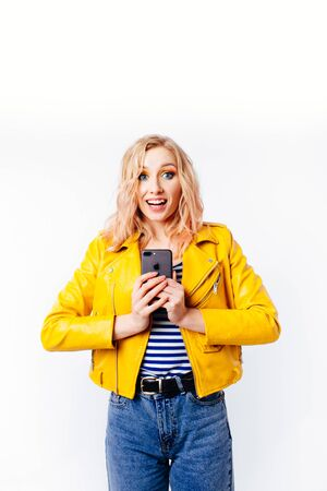 Girl in a bright yellow jacket makes a selfie for social networks on the smartphone. Banco de Imagens - 124983069
