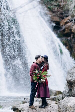 A loving, stylish, young couple in love on the background of a waterfall.