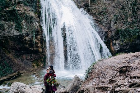 A loving, stylish, young couple in love on the background of a waterfall. Archivio Fotografico - 124983121